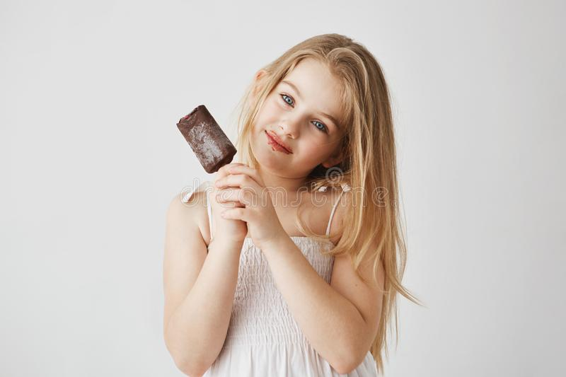 Studio portrait of joyful little girl with blue eyes and light hair enjoying her ice-cream with chocolate remains on her stock photography