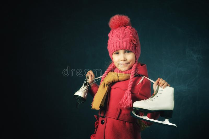 Studio portrait of a little girl in a jacket and knitted hat on a dark background. Child holding skates royalty free stock images