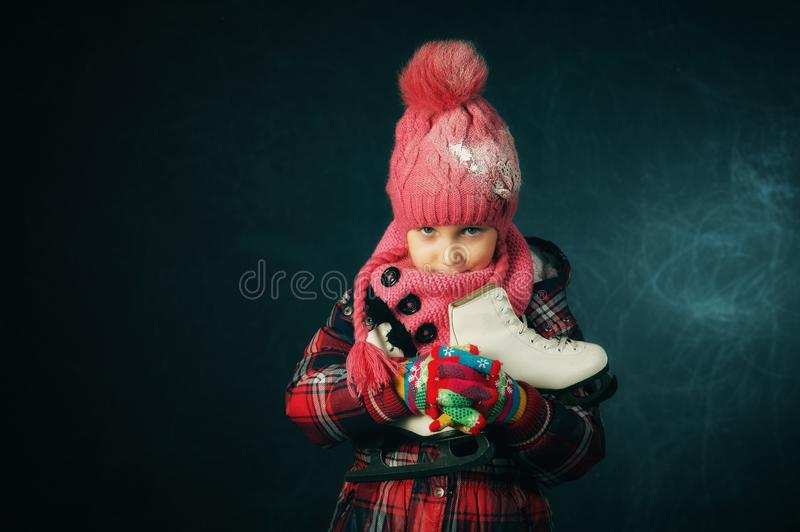 Studio portrait of a little girl in a jacket and knitted hat on a dark background. Child holding skates royalty free stock photos