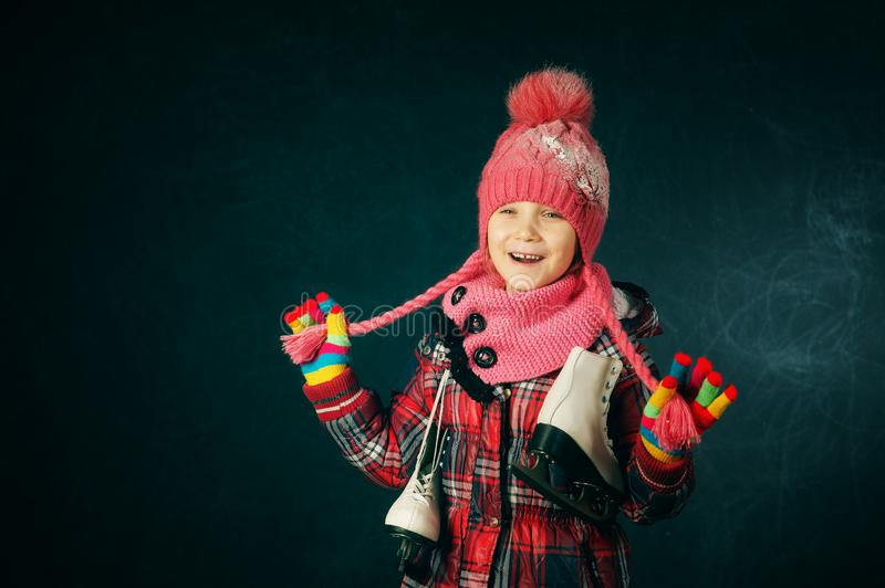 Studio portrait of a little girl in a jacket and knitted hat on a dark background. Child holding skates royalty free stock photography