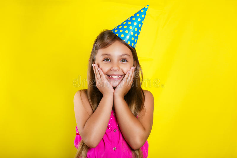 Studio portrait of a little girl wearing a party hat on her birthday. Cute girl Having fun stock photo