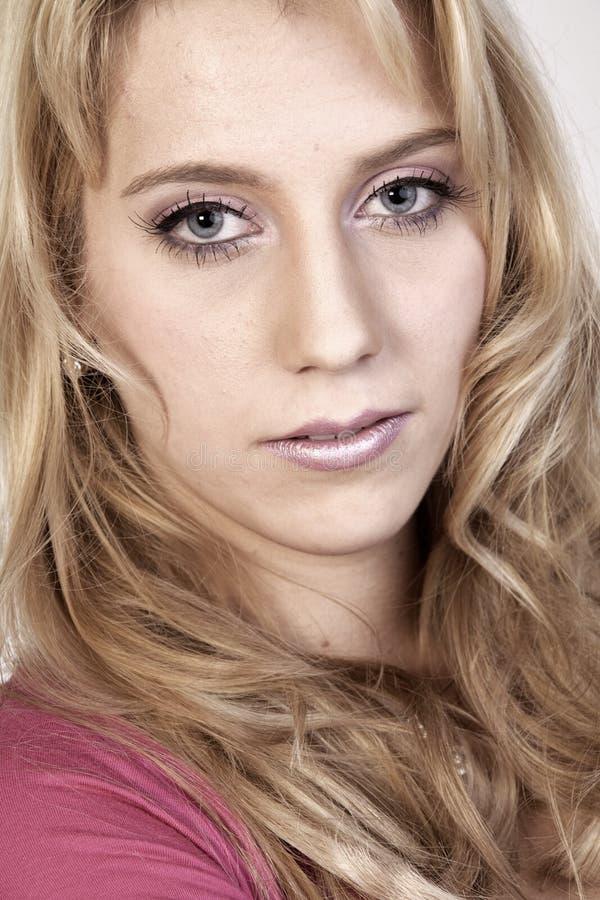 Studio portrait of a long blond girl looking hurt