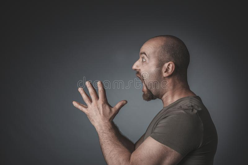 Studio portrait of a man with surprised expression clasped hands royalty free stock photography