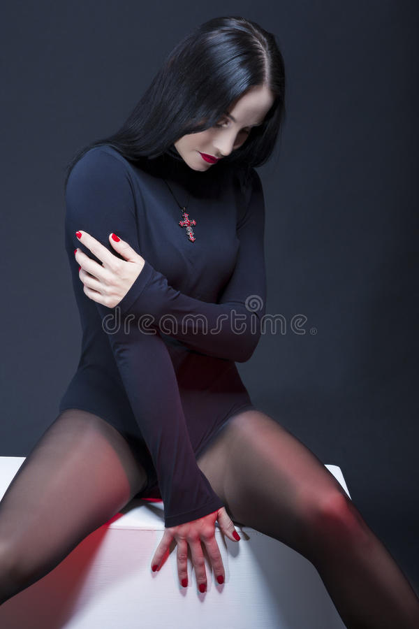 Studio Portrait of Mid Aged Relaxed Caucasian Brunette Woman Posing in Black Body Suit royalty free stock photos