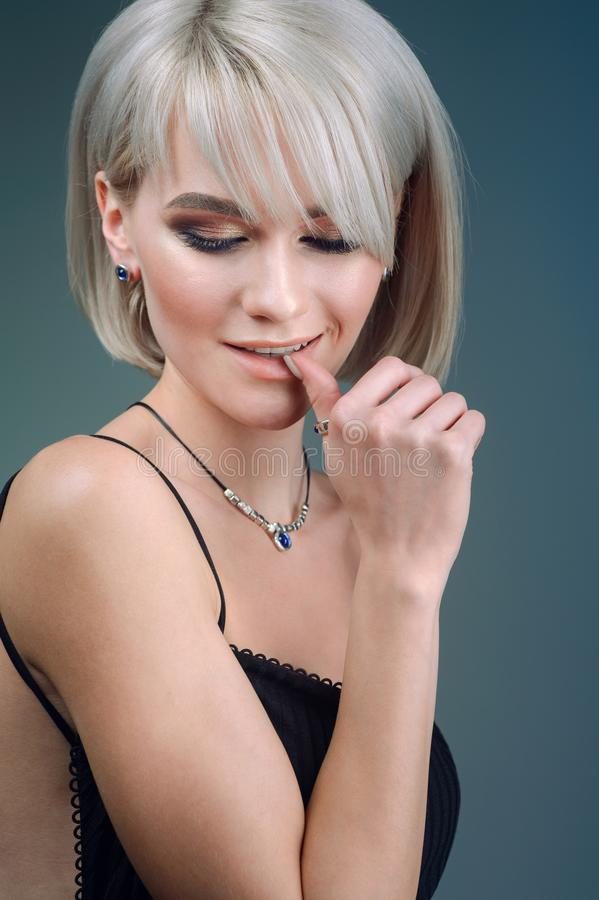 Studio portrait of a model with blond hair, showing off a necklace. Spring collection of accessories and decorations royalty free stock image