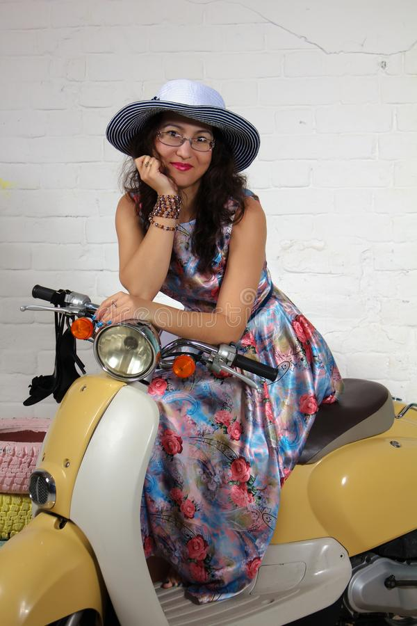 Studio portrait of a pretty asian woman sitting on scooter looking on camera stock image