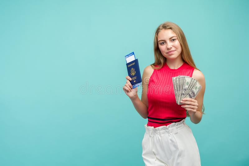 Studio portrait of pretty young student woman holding passport with tickets and money. Isolated on bright blue background royalty free stock image