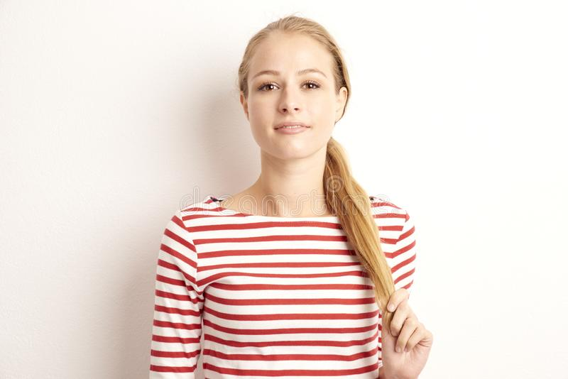 Studio portrait of pretty young woman lookig at camera and smiling while standing at isolated white background and playing with. Her hair stock image
