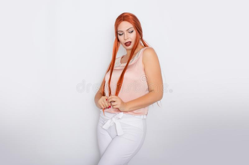 Studio portrait of a red-haired woman with long hair. Business clothes - white pants and light pink blouse with pearls stock photos