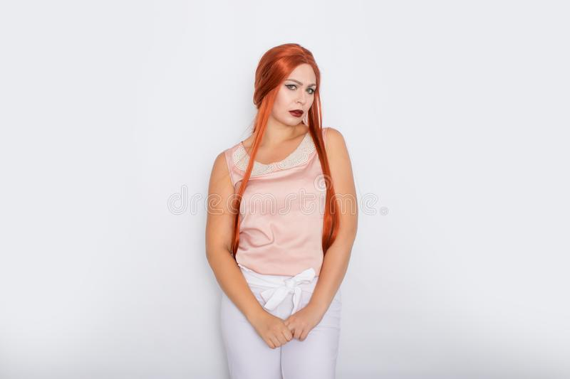 Studio portrait of a red-haired woman with long hair. Business clothes - white pants and light pink blouse with pearls stock image