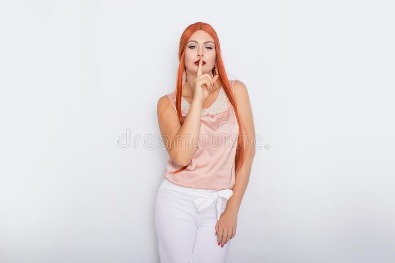 Studio portrait of a red-haired woman with long hair. Business clothes - white pants and light pink blouse with pearls royalty free stock photos