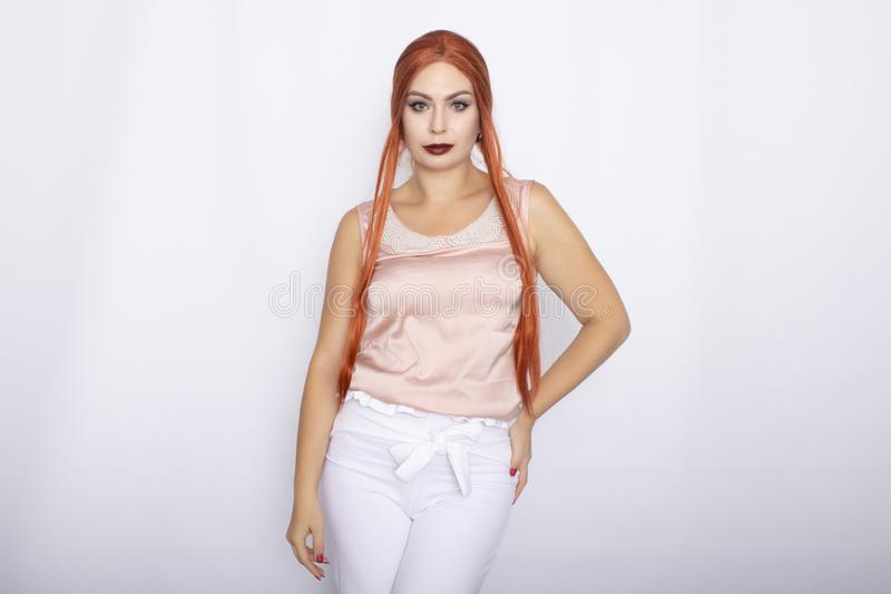 Studio portrait of a red-haired woman with long hair. Business clothes - white pants and light pink blouse with pearls stock photography