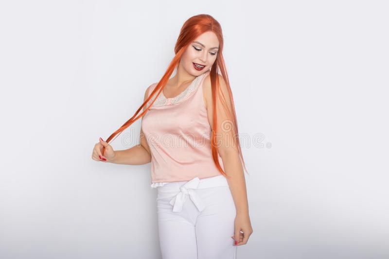 Studio portrait of a red-haired woman with long hair. Business clothes - white pants and light pink blouse with pearls stock photo