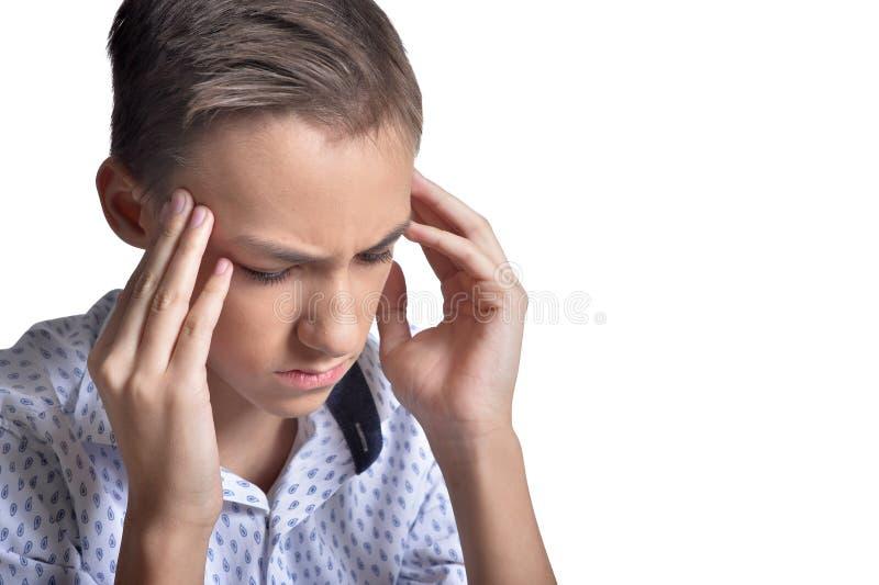 Studio portrait of sad teenage boy with headache on white background royalty free stock photos