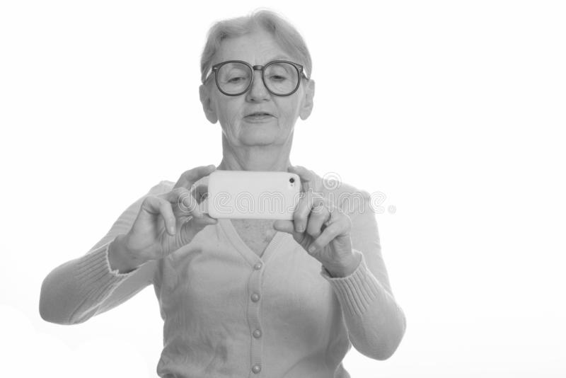Senior nerd woman taking picture with mobile phone royalty free stock photography