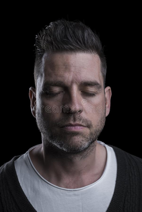 Portrait of a man with closed eyes. Isolated on black background. Vertical. Closeup stock photography