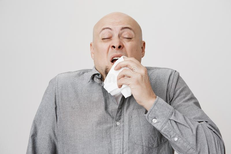 Studio portrait of sick bald caucasian man holding napkin or tissue, trying to cover mouth while sneezing with closed royalty free stock photos