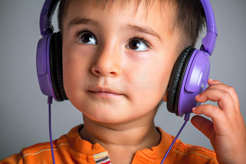 Studio portrait of a small funny boy with brown eyes in headphones listening to music on a gray background, emotions of joy, surpr. Ise stock photography