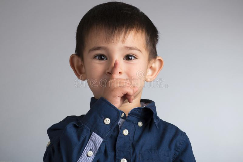 portrait of a small funny boy face showing a finger gesture: quiet royalty free stock photography