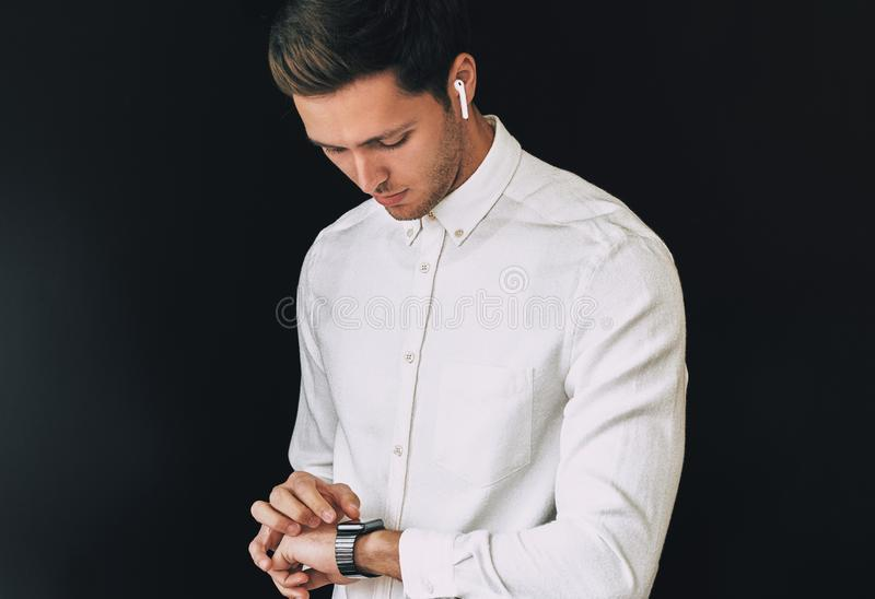 Studio portrait of smart young man wearing white shirt, looking at smartwatch posing over black background hurry up for meeting. stock images