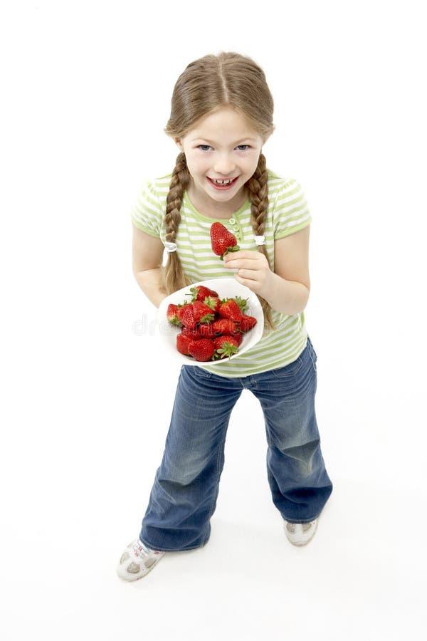 Studio Portrait of Smiling Girl Holding Bowl of St stock photo
