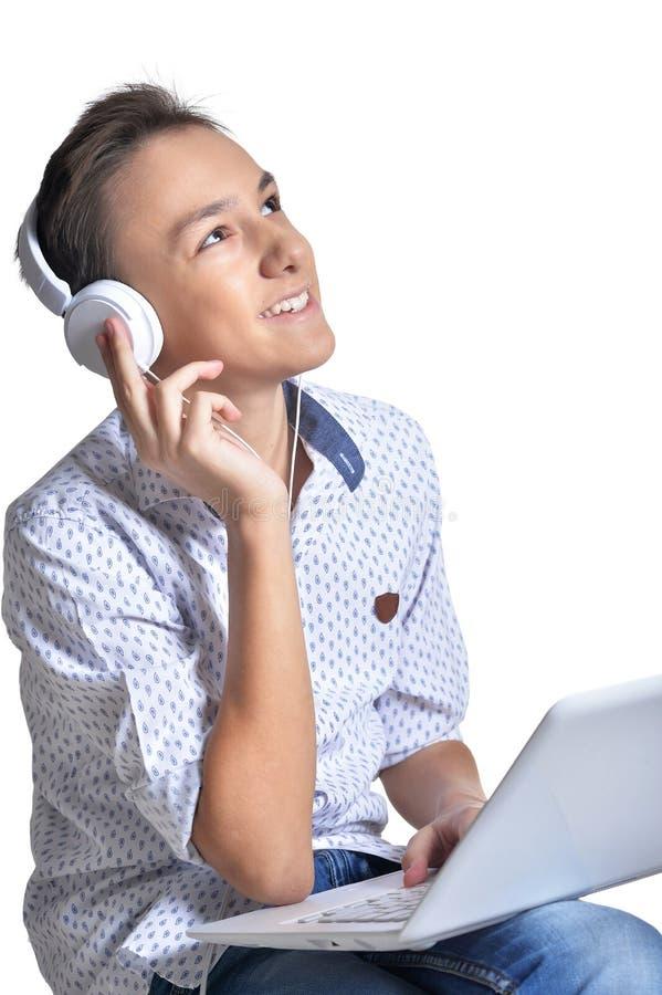 Studio portrait of teenage boy with headphones using laptop on white background royalty free stock photo