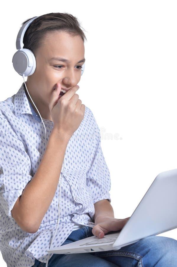 Studio portrait of teenage boy using laptop isolated stock images