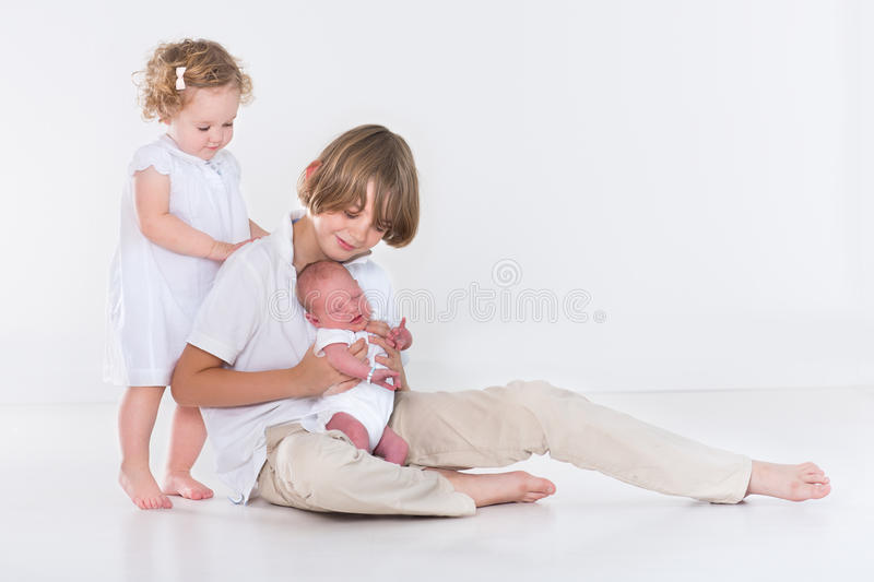 Studio portrait of three kids with white clothes. Studio portrait of three kids, teenage boy, his toddler sister and a newborn baby brother on white background royalty free stock photos