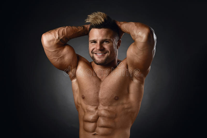 Studio portrait of topless muscular sportsman smiling over black royalty free stock images