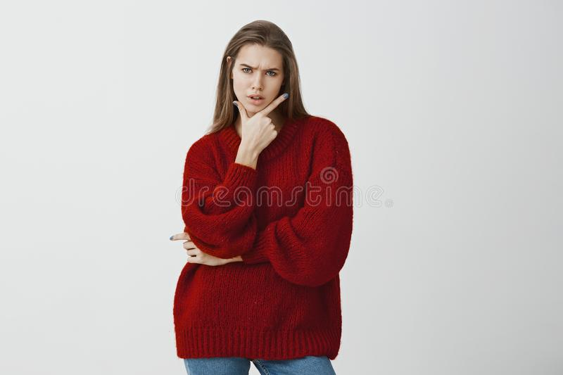 Studio portrait of troubled doubtful attractive woman in stylish red loose sweater, holding gun gesture on chin and. Frowning, feeling suspicious and frustrated stock photography