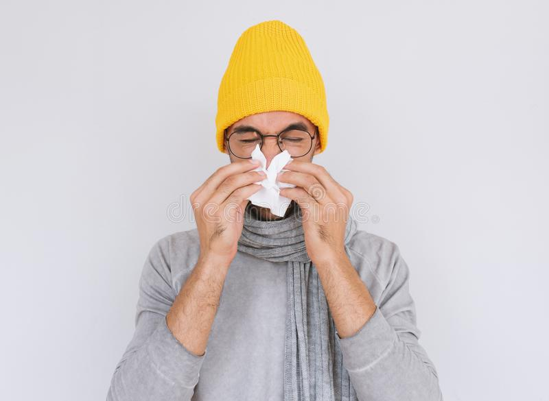 Studio portrait of unhealthy handsome man wearing grey sweater, yellow hat and glasses, blowing nose into tissue. Male have flu,. Virus or allergy. Healthy stock photography