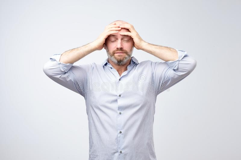 Studio portrait of upset worried sad, depressed, tired man with a headache and very stressed face royalty free stock images