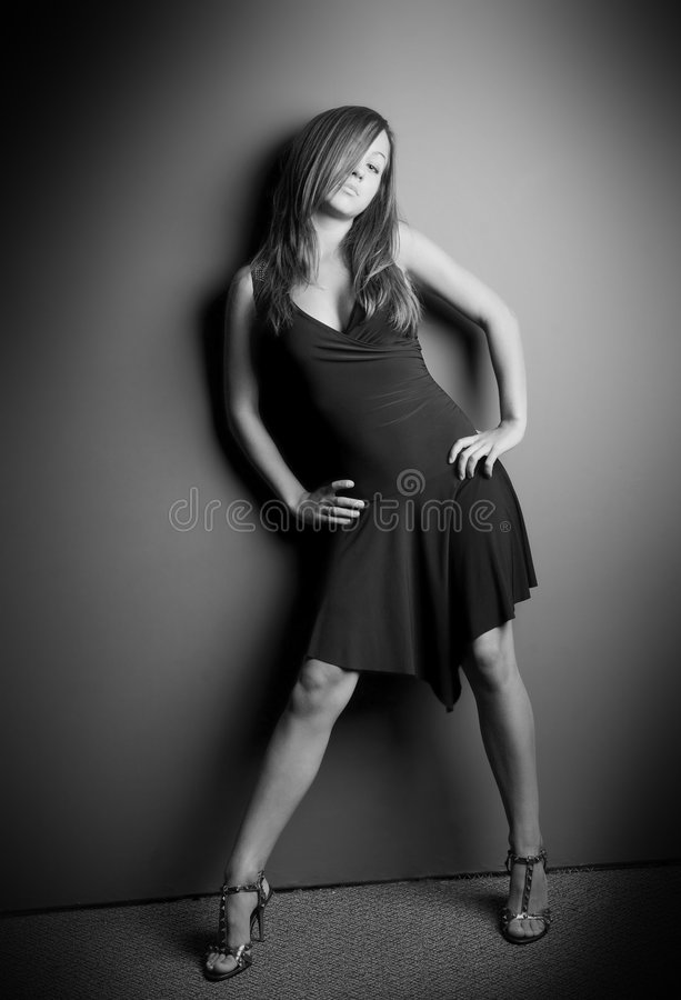 Studio Portrait of a Woman. Black and white, full-length portrait of a young woman bending slightly with hands on hips in a short dress stock images