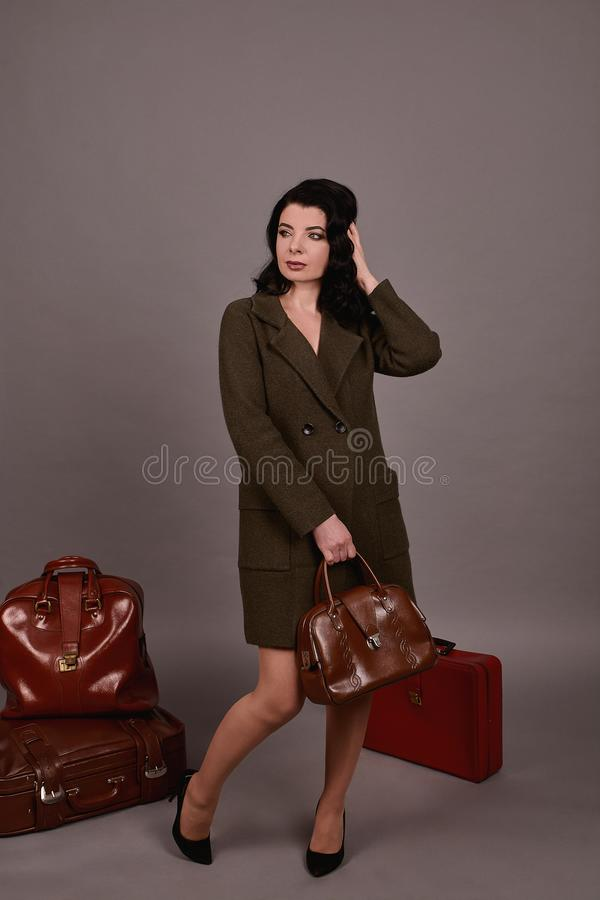 Studio portrait of a woman in classic coat posing with set of retro suitcases and hand bag on a gray background royalty free stock photos