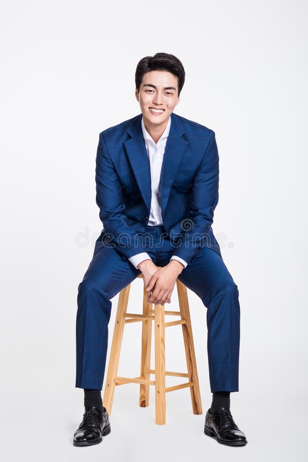 Studio portrait of a young Asian business man sitting in a chair. Shot stock photography