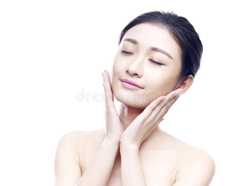 Studio portrait of young asian woman. Studio portrait of a young asian woman, eyes closed, hands on chins, on white royalty free stock photo