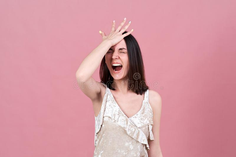 Studio portrait of a young attractive brunette woman screaming from stress and pressing her palm to her head. royalty free stock images