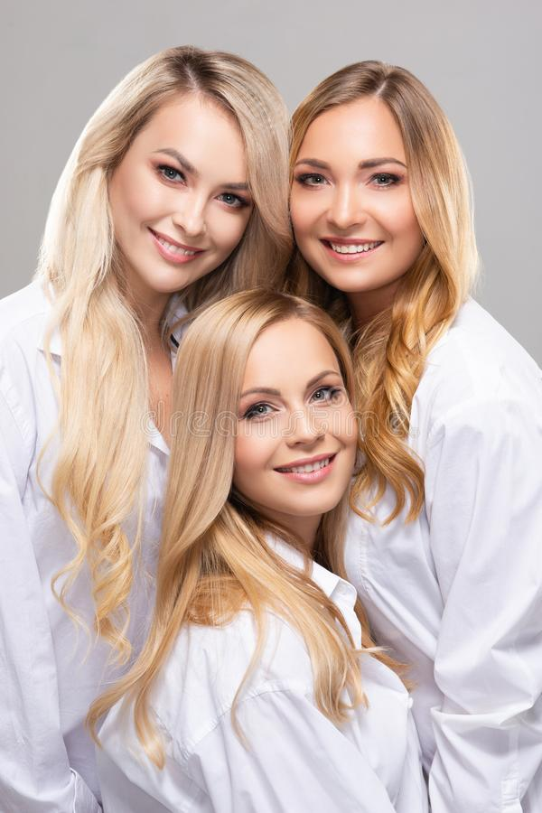 Studio portrait of young, beautiful and natural blond women over grey background. Close-up of smiling girls. Face stock image