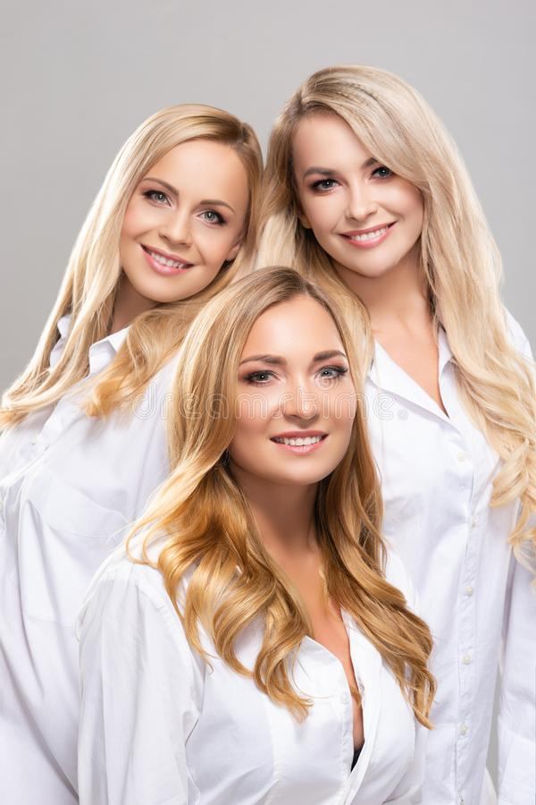 Studio portrait of young, beautiful and natural blond women over grey background. Close-up of smiling girls. Face royalty free stock image
