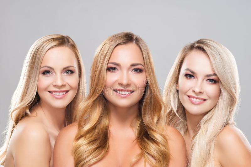 Studio portrait of young, beautiful and natural blond women over grey background. Close-up of smiling girls. Face royalty free stock photos