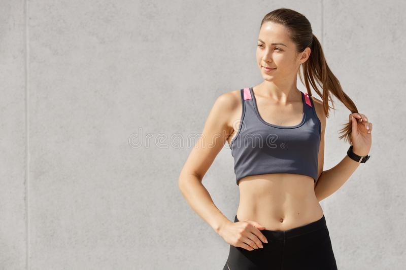 Studio portrait of young beautiful sporty woman, wearing gray sports top and black leggins, touches her pony tail, posing after. Training, looking aside, keeps stock images