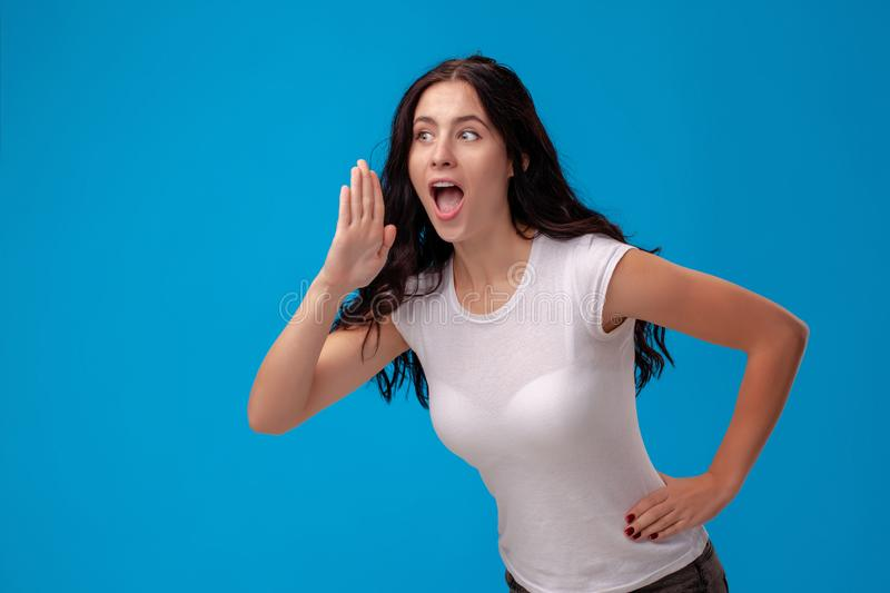 Studio portrait of a young beautiful woman in a white t-shirt against a blue wall background. People sincere emotions. stock photos