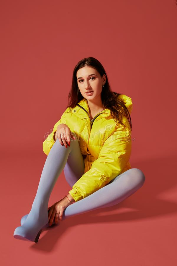 Studio portrait of young brunette woman sitting on the floor in yellow down jacket and grey blue panty hoses or royalty free stock photos