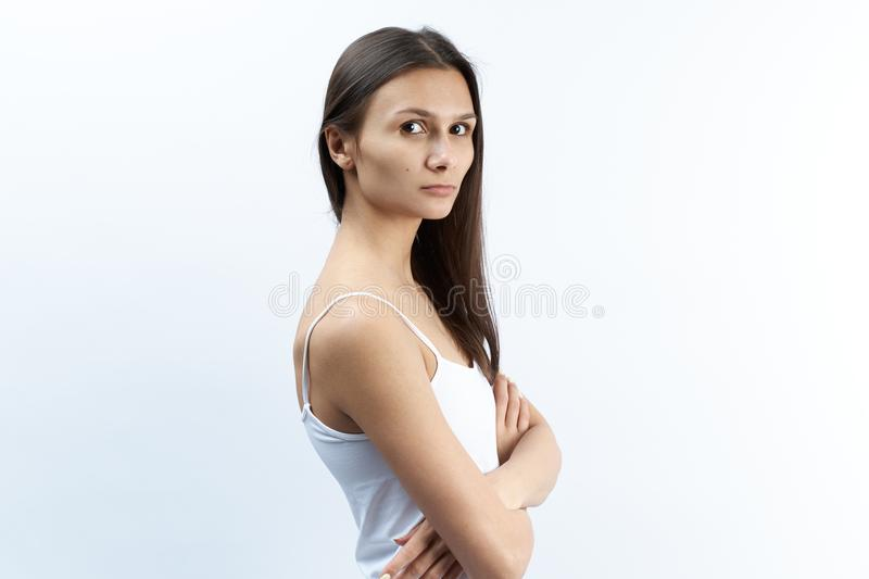Studio portrait of young Caucasian woman with serious upset dissatisfied with a puzzled expression. arms crossed over the abdomen. stock photos