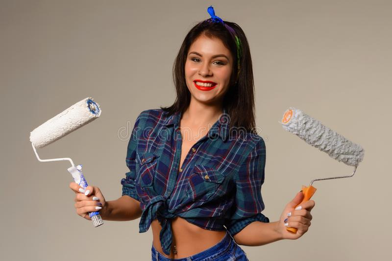 Studio portrait of young cheerful brunette girl with paint roller royalty free stock image