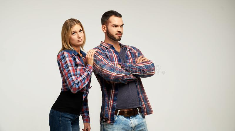 Studio portrait of a young couple in casual plaid shirts quarreled and taking a step towards reconciliation. stock photos