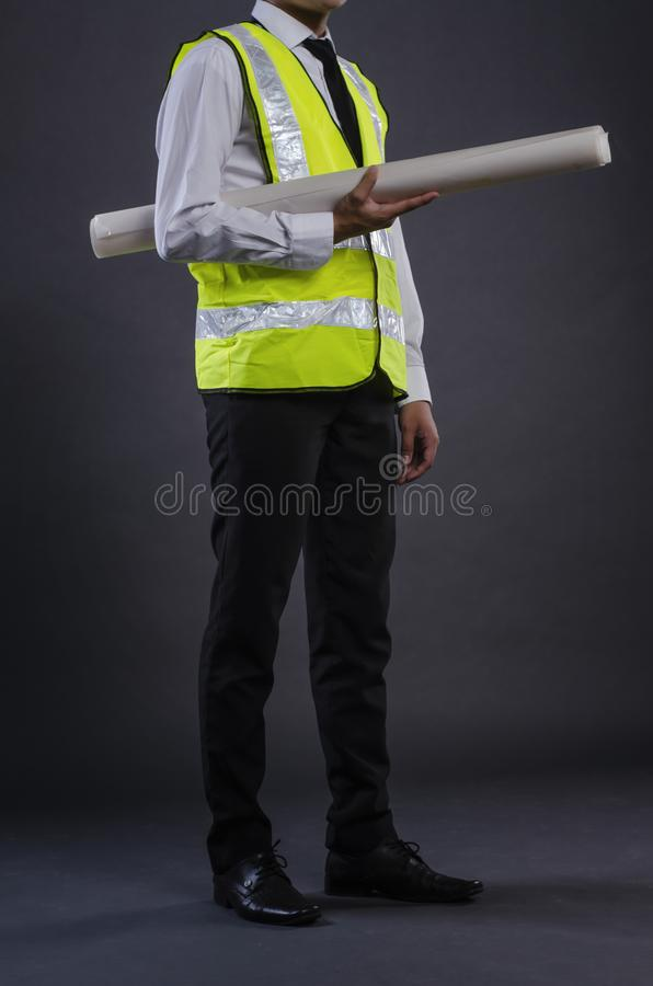 Young engineer or manager with white safety helmet holding drawing royalty free stock images