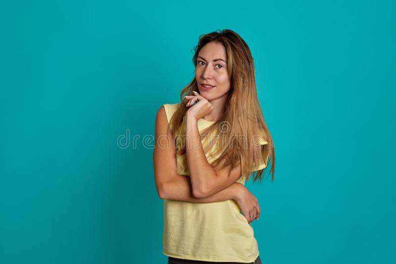 Studio portrait of a young fair-haired beautiful girl. Emotions of a girl on a blue background stock photography