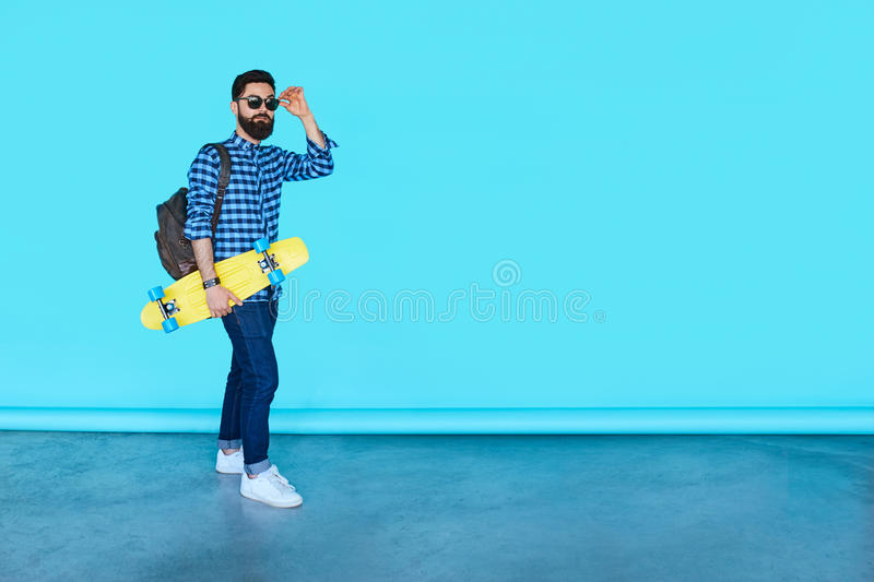 Studio portrait of young fashionable hipster man posing. Full body portrait of young fashionable hipster man posing over blue background with copy space. Bearded royalty free stock photography