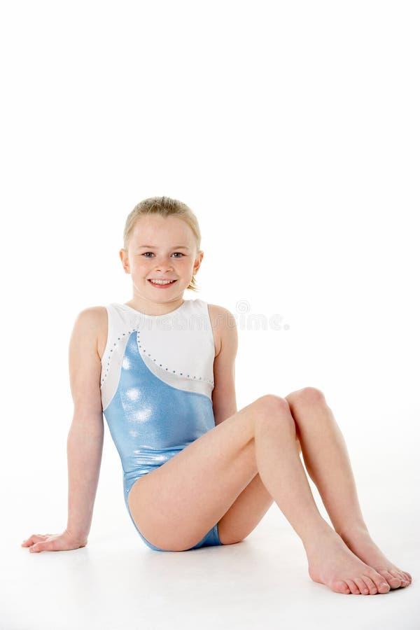 Studio Portrait Of Young Female Gymnast. Sitting on white background royalty free stock image